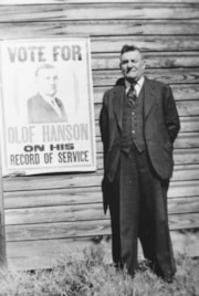 Olof Hanson stands beside a his own campaign poster (descriptions1758)