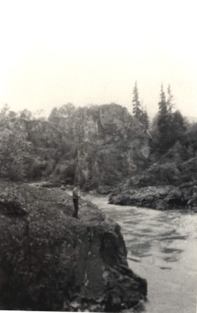 Man standing on rocks by Moricetown Canyon. (descriptions2032)