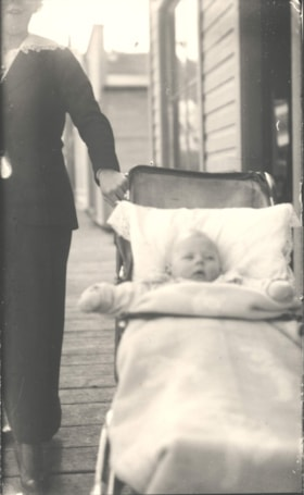 Woman standing beside a carriage with a baby, standing on t… (descriptions2198)