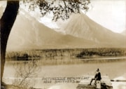MAN SITTING ON DOCK LOOKING OUT OVER THE LAKE AND ACCROSS A… (descriptions2975)