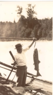 Foster Haverly holding a large salmon at Moricetown Falls, … (descriptions3823)