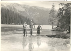 3 men at the side of a river with long poles. (descriptions4380)