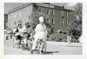 Three unidentified people on a three-person bike outside th… (descriptions6582)