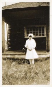 Photograph of Marguerite Wood in front of a house (descriptions6923)